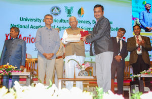 Dr Rachit Saxena receiving the Young Scientist Award from Mr Vajubhai Rudabhai Vala, Governor of Karnataka, at the XIII Agricultural Science Congress at Bengaluru. Mr Krishna Byre Gowda, Minister of Agriculture for State, Government of Karnataka; Prof Ramesh Chand, Member, NITI Aayog, Government of India; and Dr Trilochan Mohapatra, Secretary, Department of Agricultural Research and Education, and Director General, Indian Council of Agricultural Research, Government of India, were also present. Photo: NAAS, Bengaluru