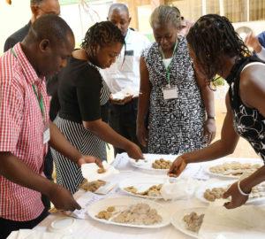 Des partenaires du projet entrain de goûter des produits à base de mil et de sorgho servis à l'heure d'une pause.