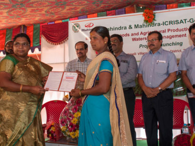 Ms Srilatha (second from left) hands over a soil test card to a woman farmer at the launch. Photo: PS Rao, ICRISAT