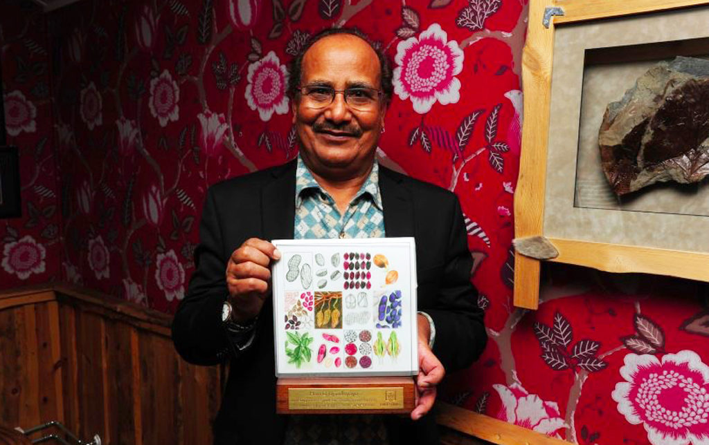 Dr Hari D Upadhyaya with a personalised award featuring artwork by Sophie Munns. Photo: The Crop Trust