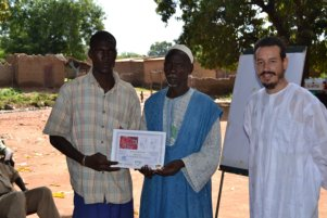 Mr. Boli Burama Berthe, a farmer in Sukumba, receives his award from Mr. Yakuba Berthe. The certificate includes a map insert of the crop response to fertilizer application, as seen by the WorldView2 earth observation satellite, and box-plots quantifying yield and biomass changes over corresponding plots.