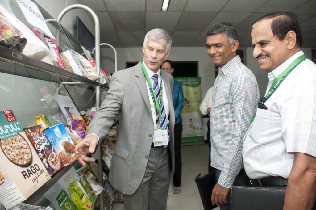 Dr Bergvinson (L) demonstrating millet products to Mr Byre Gowda. Also seen Dr Wani (R). Photo: PS Rao, ICRISAT