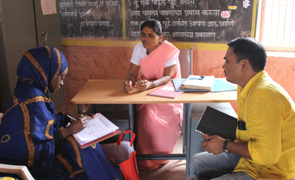 Ms Diatta (L), collecting policy information from village officials.