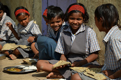 Young school children in rural India eating millet chappatis with rice and vegetable curry