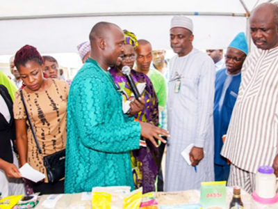 Mr Aliyu Adinoyi, Scientific Officer, explaining about displayed crops and products to Senator Lokpobiri. Photo: Hakeem Ajeigbe, ICRISAT