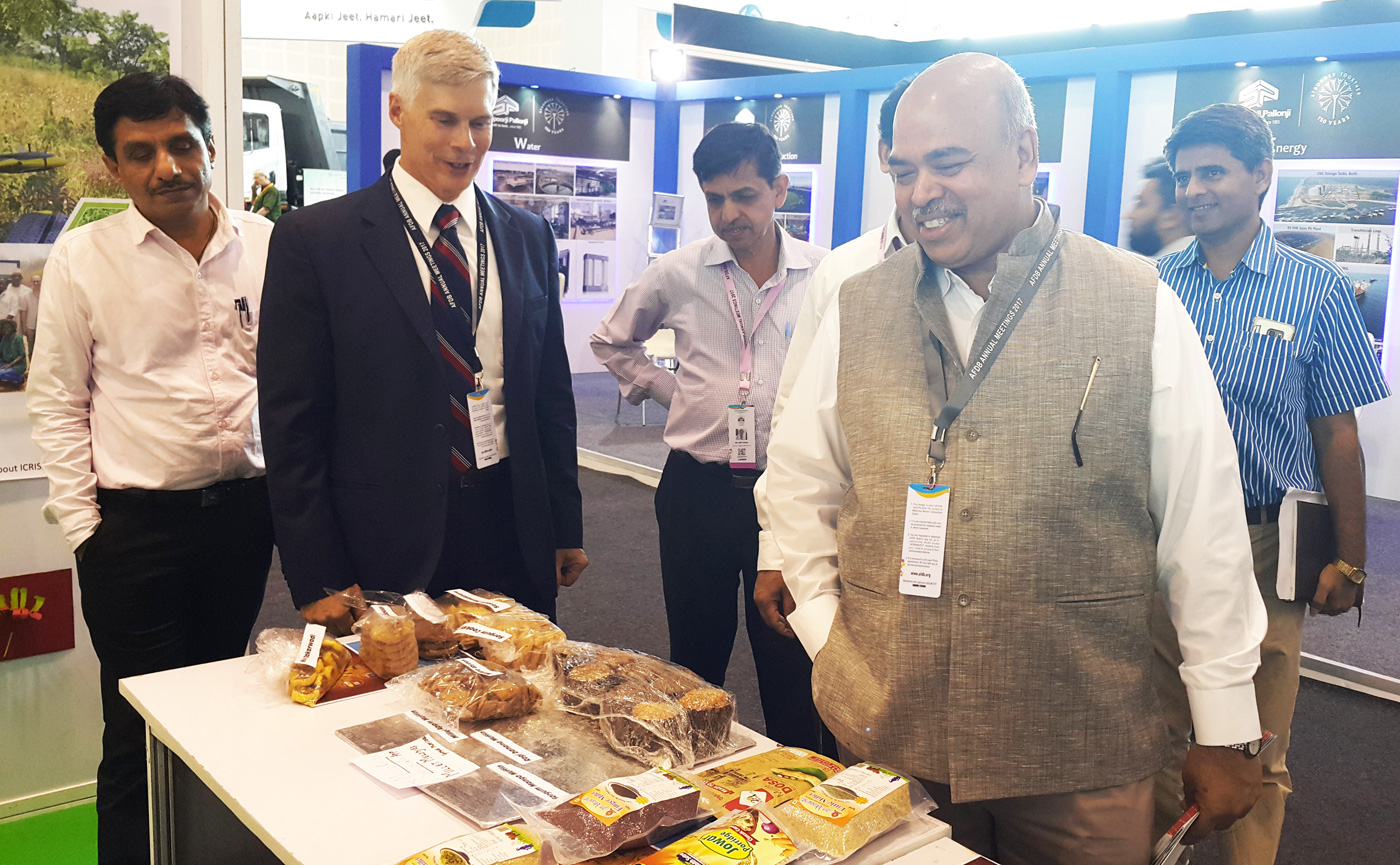 Mr SK Pattanayak (front right) inspects sorghum and millet food products at the ICRISAT stall, while Dr Bergvinson (second from left) looks on. Photo: ICRISAT