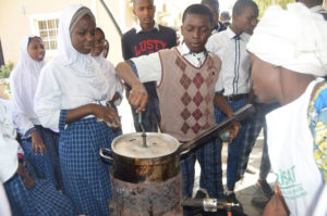 A young student tries his hand at making pop sorghum in a locally fabricated machine.