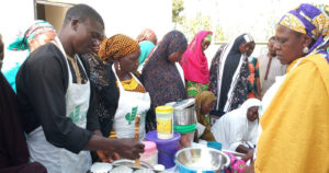 A young man mixes batter before pouring into moulds for sorghum cakes in Bida-Badeggi SCPZ, Northern Nigeria. Photo: F Akinseye, ICRISAT