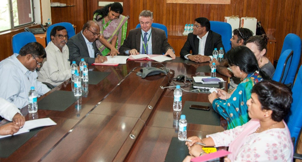 Prof Ch Gopal Reddy, Registrar, Osmania University, and Dr Peter Carberry, Director General, ICRISAT, sign the MoU as Vice-Chancellor Prof S Ramachandram (to Dr Carberry's left) looks on. Photo: PS Rao, ICRISAT