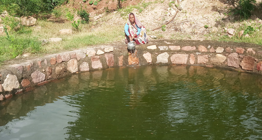 A woman collects water at a well that was recharged due to water harvesting in Lalitpur district of Bundelkhand. Photo: Shishuvendra K, ICRISAT