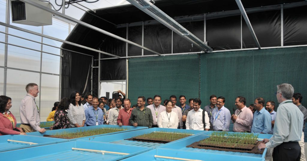 ICRISAT scientists at the polyhouse after its opening on Friday. The facility can be seen with the canopy folded and under naturally lit conditions.