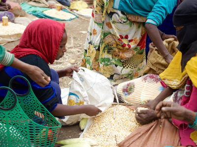 A woman sells maize at the market in Sidameika Tura, Arsi Negele, Ethiopia. Photo: Peter Lowe, CIMMYT